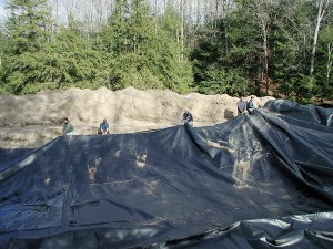 Tumber's crew shimmies a huge rubber liner into place at the Mansfield site. Photo Courtesy Tumber & Associates.