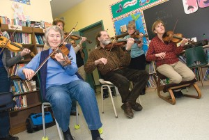 Sue Meggs, Peter Cole, Barb Terrett and Nancy Urekar (above, foreground) and Sam Nassey (left) brush up on their fiddle techniques at a recent weekend workshop held by Bill Elliott at The Maples near Orangeville. Photo by Tom Partlett.