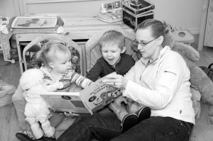"Jennifer Van Winden reads with her children Sarah and Tommy. After attending the Feelings After Birth program, she came to realize that ""being a great mom is an evolution, not an inborn trait or something you can learn from a book."" Photo by Pete Paterson."