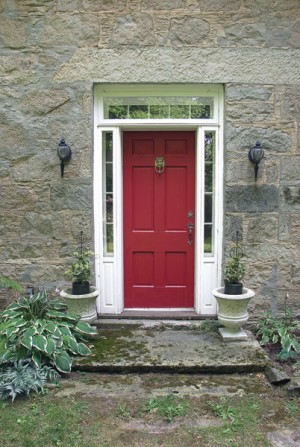 """We painted the door of the original house red to differentiate it from the neighbours,"" recalls Janet. ""Few pay much attention to street numbers in the country. There's a stone house nearby with a yellow door. We tell visitors, we're the stone house with the red door and that seems to get them here."" Photo by Rosemary Hasner."