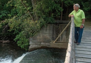 Nelson, now 86, continues to live nearby and still visits his former home. Below he surveys the mill dam from the bridge he helped his father build.