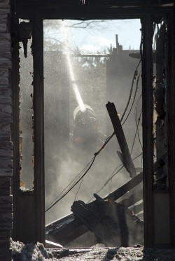 Grand Valley firefighter works on hot spots at an Amaranth house. Photo by Brandon Muir