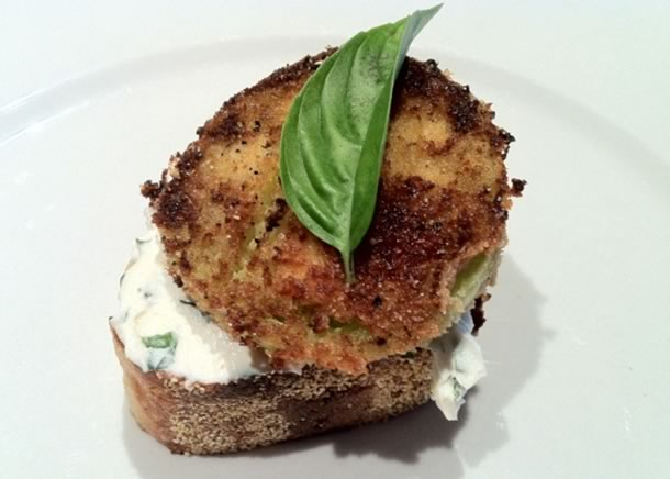A basil infused cream cheese spread tops a fried crostini and topped with a buttery fried green tomato.