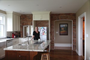 Erica Hyland in her kitchen, where the original brick walls have been exposed.