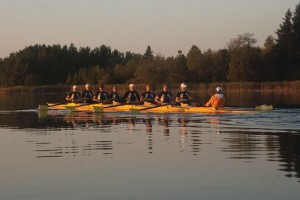 Dawn casts a golden glow on Island Lake rowers, from bow to stern, Brent Kane, Ken Norris, Bryan Corlett, Jack Lacrooy, Shane Curry, Steve Fisher, Aleks Lietz , Richard Reid, and coxie Janet Reid. Photo by Rosemary Hasner.