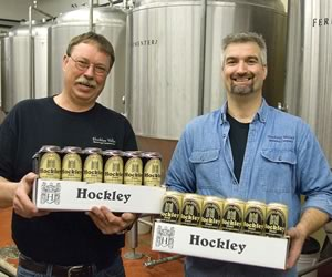 John Christie and Andrew Kohnen hoist some two-fours fresh from the brewery's shiny new canning machine. Photo by Pete Paterson.