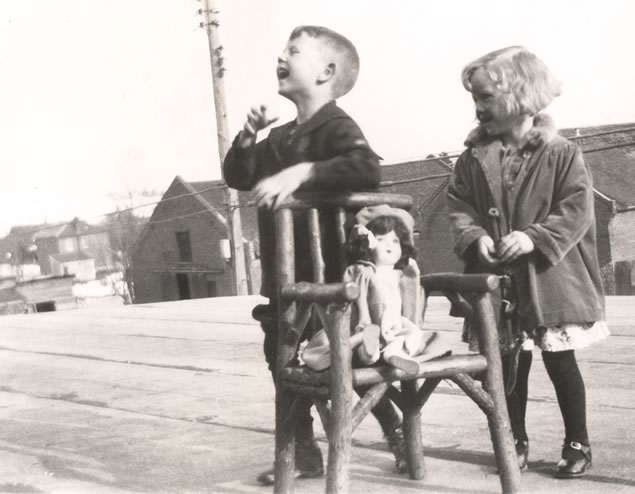 Eleanor, her brother Howard, and her Eaton's Beauty Doll, playing on the first-floor roof at the rear of the hotel, overlooking the barns. Photo Courtesy Eleanor Mcmillan Jamieson.