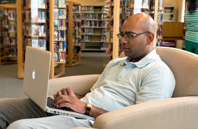 Anil Sharma takes advantage of the library's Wi-Fi. Photo by Pete Paterson.