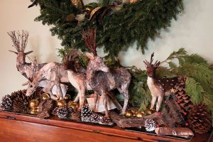 Handcrafted birchbark deer romp on a mantel among painted cones and miniature Christmas trees. Photo by Pete Paterson.