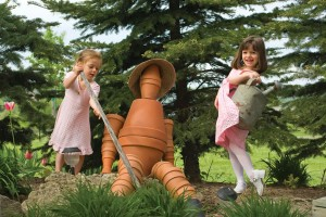 Katariina Perreault, 3, and Danielle Fracassi, 5, make friends with the Clay Pot Man in the Kids' Garden. Photo by Pete Paterson.