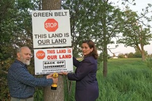 Ian Sinclair and Lynne Moore, both members of the Peel-Halton Landowners Association, erect one of the organization's signs. The signs, with their bold message, have sprung up on farm fences around the countryside. Photo by Pete Paterson.
