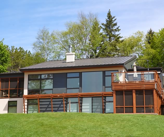 The clean modern lines of the house make a strong impression while the windows reflect the seasons.