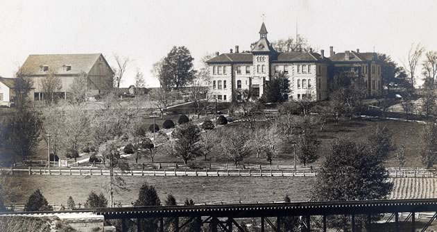 The Wellington County House of Industry and Refuge as seen from the south side of the Grand River, c. 1907–1914. Photo courtesy of Wellington County Museum & Archives, PH 10814.