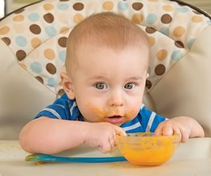 Samuel Grime enjoys his first taste of solid food. Photo by Pete Paterson.