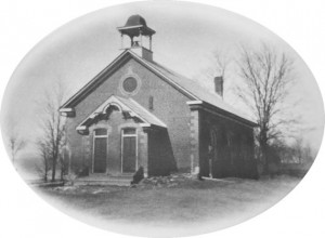 : An historic photo of the school before the maples, planted by students, grew to tower over it.