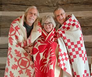 Wearing their story on their backs, author Shelagh Roberts (in Cockscomb) is flanked by quilt photographer Pete Paterson (in Oak Leaf and Reel) and archivist Steve Brown.