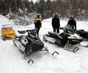 Three men snowmobiling