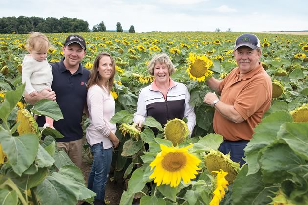 """Sean and Amy Davis with baby Nora and Sean's parents Joanne and John amid sunflowers they grow for birdseed at Davis Feed & Farm Supply. """"2013 is the year I'll never forget because we had four generations living on this farm,"""" says Sean. Photo by Pete Paterson."""