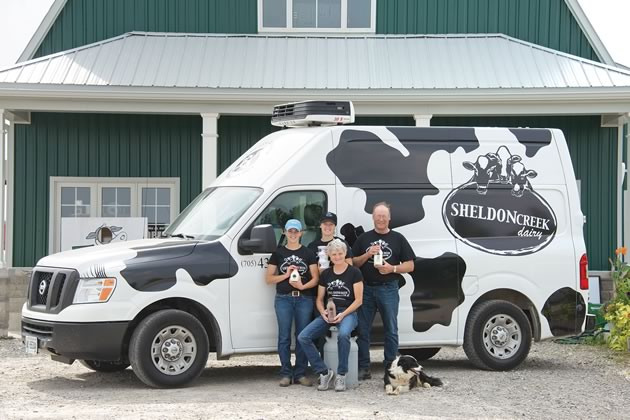 Sisters Emily and Marianne den Haan (left) with their parents John and Bonnie and dog Megs at Sheldon Creek Dairy, one of the first three dairies in Ontario since the 1960s licensed to sell their own whole milk direct from their farm. Photo by Pete Paterson.