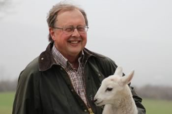 Dan Needles with a lamb. Photo by Lindan Courtemanche.
