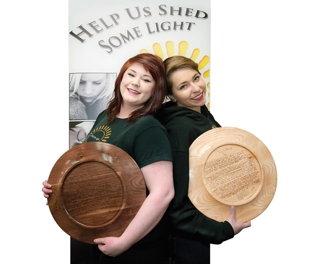 Robin Blakely (left) and Hailey Harrigan show off the plates made by wood turner Jim Lorriman and inscribed with their stories. As members of Shed the Light, the young women tell their personal stories at local schools to reassure other young people who struggle with mental health that they are not alone. Photo by Rosemary Hasner / Black Dog Creative Arts.