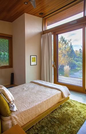 This bedroom overlooks the pond and fills with early morning light. Photo by Pam Purves.