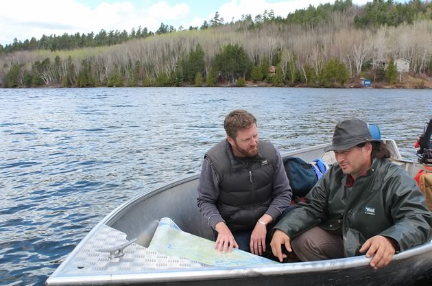 John Millar (left) and Dan Mongrain check a map to decide the best place to take water samples from Lake Temagami. Bear Island in the background is home to Temagami First Nation. Courtesy Tin Roof Global.