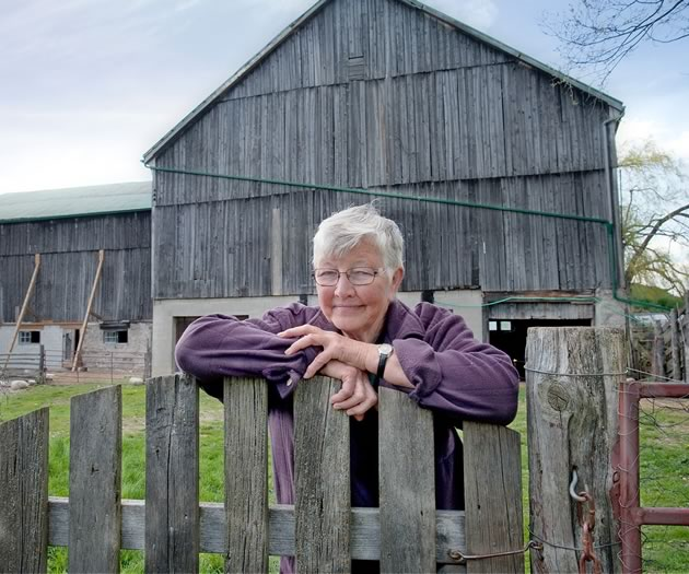 Longtime resident Brenda Dolling takes a rare break in front of the property's heritage barn. Photo by Rosemary Hasner / Black Dog Creative Arts.
