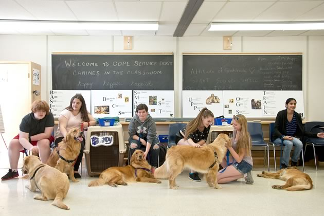In the classroom (bottom – left to right), Sheldon with Kaiko, Michaela with Winston, Hanna with Brandy, Hannah Claire, Alyssa with Luna, and Sukhmeni with Sunny take a moment to relax during a training session with the dogs. Photo by Pete Paterson.