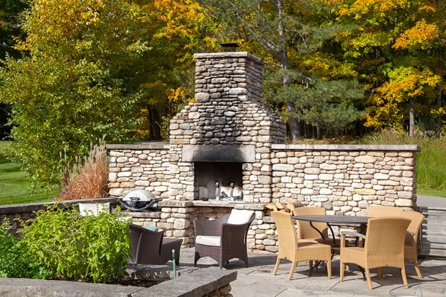 A substantial outdoor fireplace is built into the dry-stone wall that encloses a vegetable garden and outdoor dining area. Photo by Pam Purves.