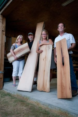Cindi Dormer, Tony Dormer, Dianne Hoegler and Jedson Smuck of Deep Water Wood show off wood planks retrieved from the depths of Georgian Bay. Photo by Rosemary Hasner / Black Dog Creative Arts.