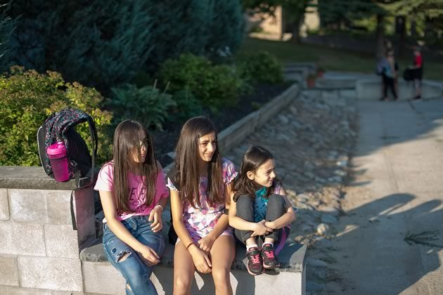 Emelia, Kamilia and Marry-Rose Talia wait for the bus on their first day of school this fall. Photo by James MacDonald.