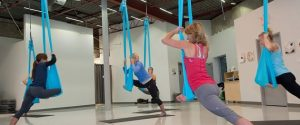 An aerial yoga workout, like this one at Personal Best in Mono Mills, combines yoga, Pilates and dance. The silk hammock allows for extra stretch and the occasional thrill of weightlessness. Photo by Rosemary Hasner / Black Dog Creative Arts.
