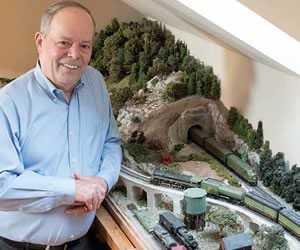 Retired broadcast journalist Hap Parnaby in his third-floor train room. The tracks circle the room through an elaborate landscape he handcrafted. Photo by Pete Paterson.