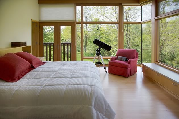 The bedroom has sweeping glass walls with no need for curtains. Photo by Pam Purves.