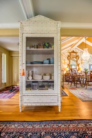 A new acquisition, the antique dish cupboard adds to the eclectic decor. Photo by Pam Purves.