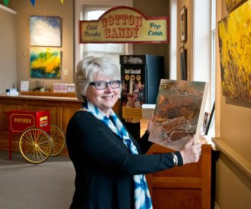 Susan Reynolds holds a painting by Cathy Dalton, one of the artists in a recent show Susan curated in the lobby of Theatre Orangeville. Photo by Pete Paterson.