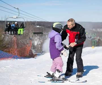 Neil O'Donnell checks in with a young skier. Photo by James MacDonald.