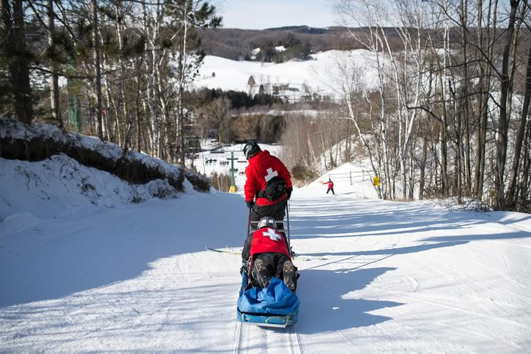 In their distinctive red and white vests, ski patrollers make a run with the rescue toboggan at Hockley Valley Resort. Photo by James MacDonald.