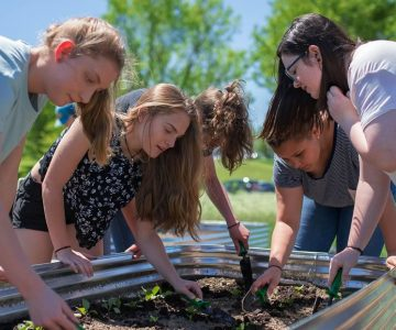 A sunny spring day gets students Sarah Baker, Megan Crane, Maggie Claus, Mikayla Clarke and Amanda Cote outside to plant fast-growing crops such as red leaf lettuce, spinach and kale. Photo by James MacDonald.