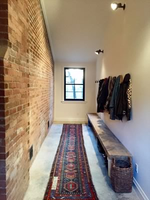 The home's mudroom features exposed brick, a new window, a long wooden bench and a vintage rug. Photo by Nat Caron.