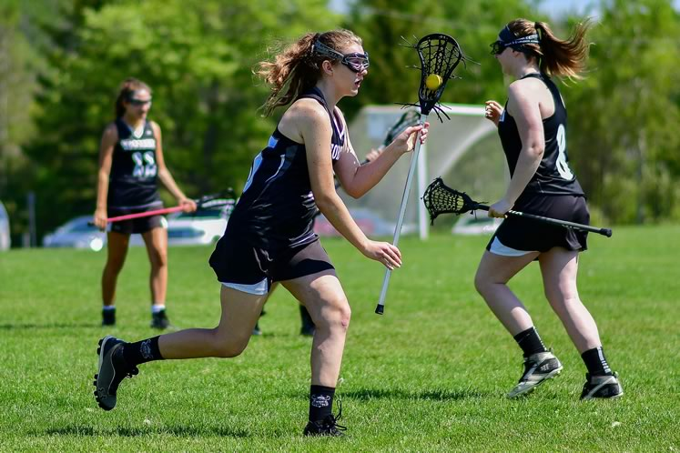 Northmen women's U19-1 field lacrosse players Chloe Miller, Cassidy Anyon, and Sophie Skillen play a game on Barbour field in Hillsburgh against a team from Orillia last June. Photo by James MacDonald.