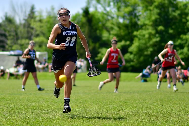 Northman women's U19-1 field lacrosse player Chloe Miller runs the field, with player (and minor coach) Chelsea Crang in the background. Photo by James MacDonald.