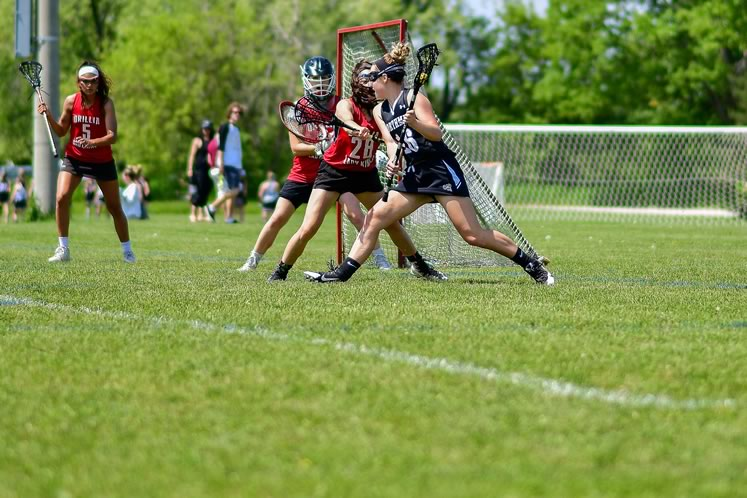 Northmen women's U19-1 field lacrosse player Jayda Rawn-Hassel faces three Orillia players. Photo by James MacDonald.
