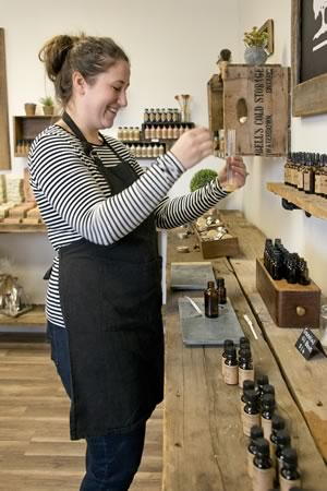 Jennifer Kleinpaste at her new store's essential oil bar where she brainstorms scent blends for future products. Jennifer or staffer Jessica Marchildon also create signature blends for customers here. Photo by Pete Paterson.