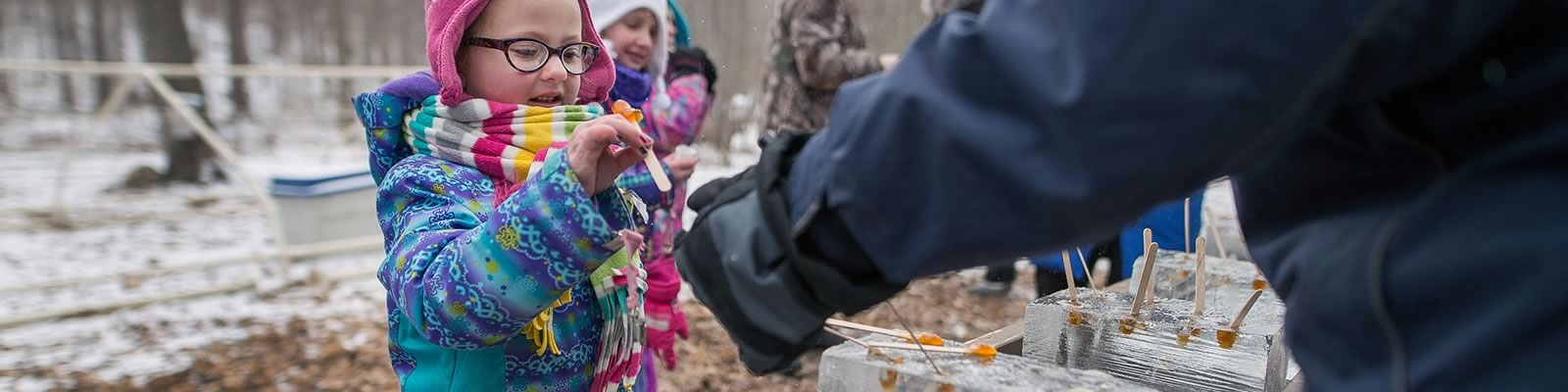 Youngsters sample maple candy at Island Lake last spring. Photo by James MacDonald.