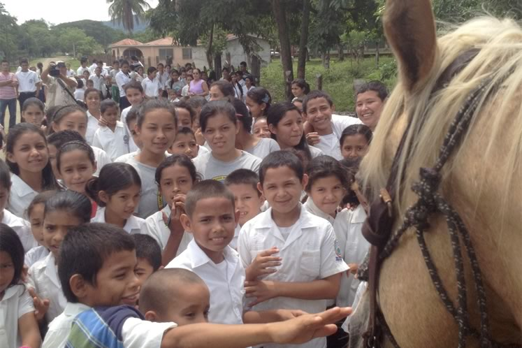 On a rural road in Honduras, an entire school turned out to say hello to Filipe and stroke Frenchie. Courtesy Filipe Leite.