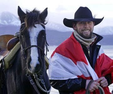 On the cold day Filipe Masetti Leite arrived on Pablo Picasso in Ushuaia at the tip of South America, he wrapped himself in a Canadian flag sent to him by Orangeville mayor Rob Adams. Photo by Barbara Nettleton.