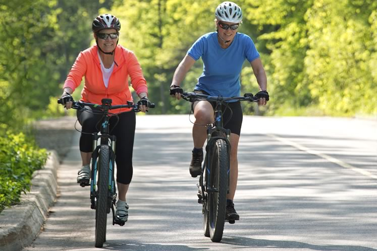 E-bike fan Liz Beatty and skeptic Nicola Ross recently took their motorized wheels for a ride on Forks of the Credit Road. Photo by Pete Paterson.