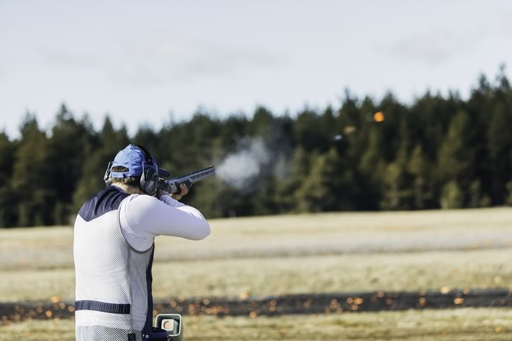 A trap shooter tests his skills with a 12-gauge pump-action shotgun. Photo by Visualspace   istockphoto.